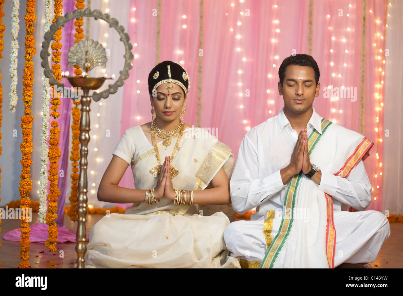 Bride and bridegroom in traditional South Indian dress praying at ...