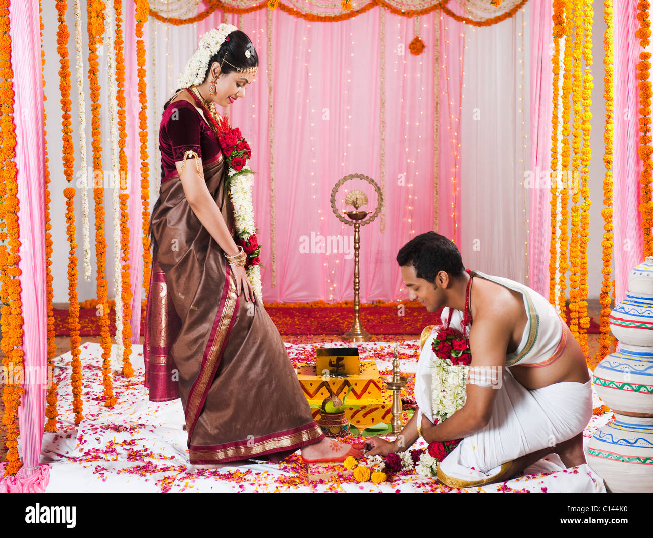 Bridegroom putting a toe ring onto the bride\'s toe during South ...