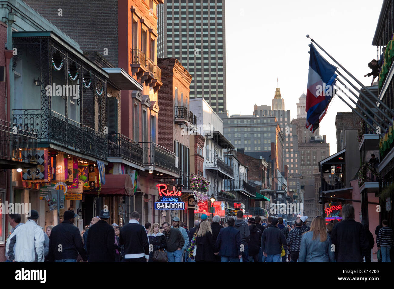 People cruising by bars and nightclubs on Bourbon Street at night in New Orleans - Stock Image