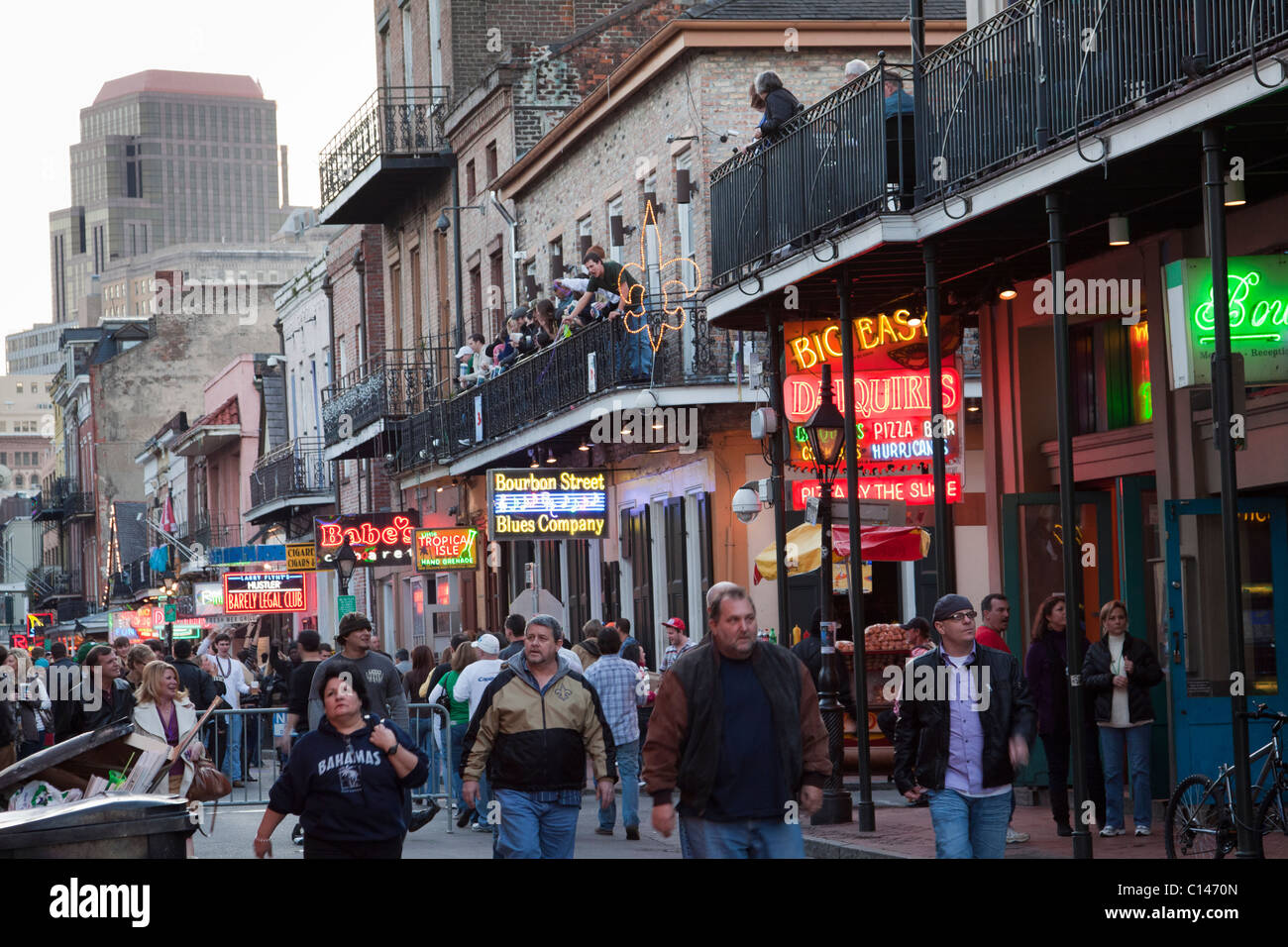 People cruising by neon signs of bars and nightclubs on Bourbon Street at night in New Orleans - Stock Image