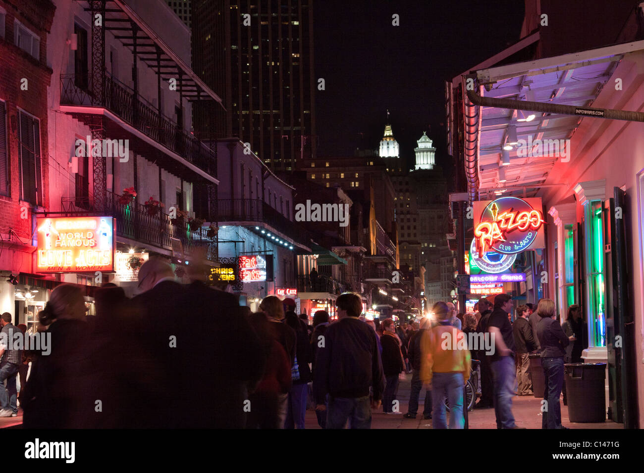 People walking along Bourbon Street in New Orleans with neon signs at night - Stock Image
