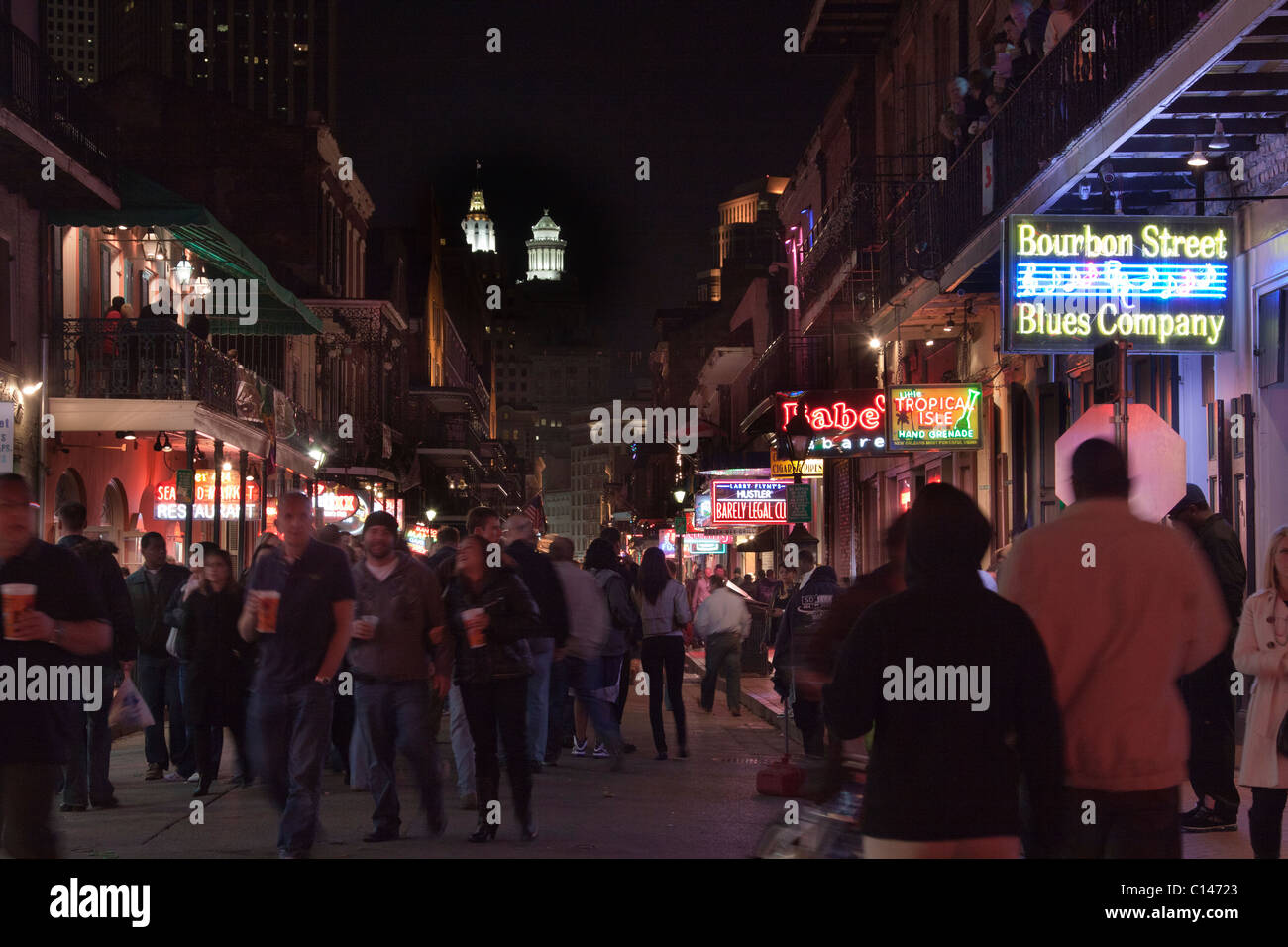 People drinking and walking along Bourbon Street in New Orleans with neon signs - Stock Image