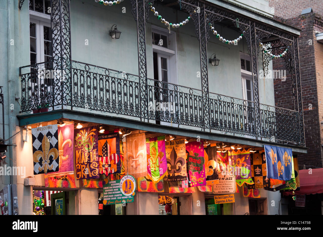 Souvenir shop with bright banners below wrought iron balcony on Bourbon Street in New Orleans - Stock Image