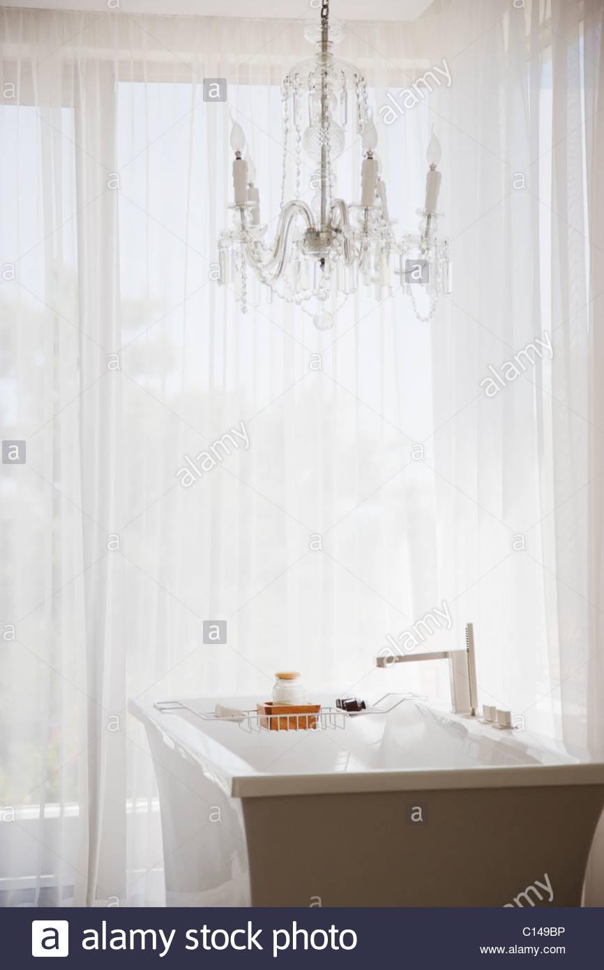 Elegant chandelier and modern bathtub in bathroom stock photo