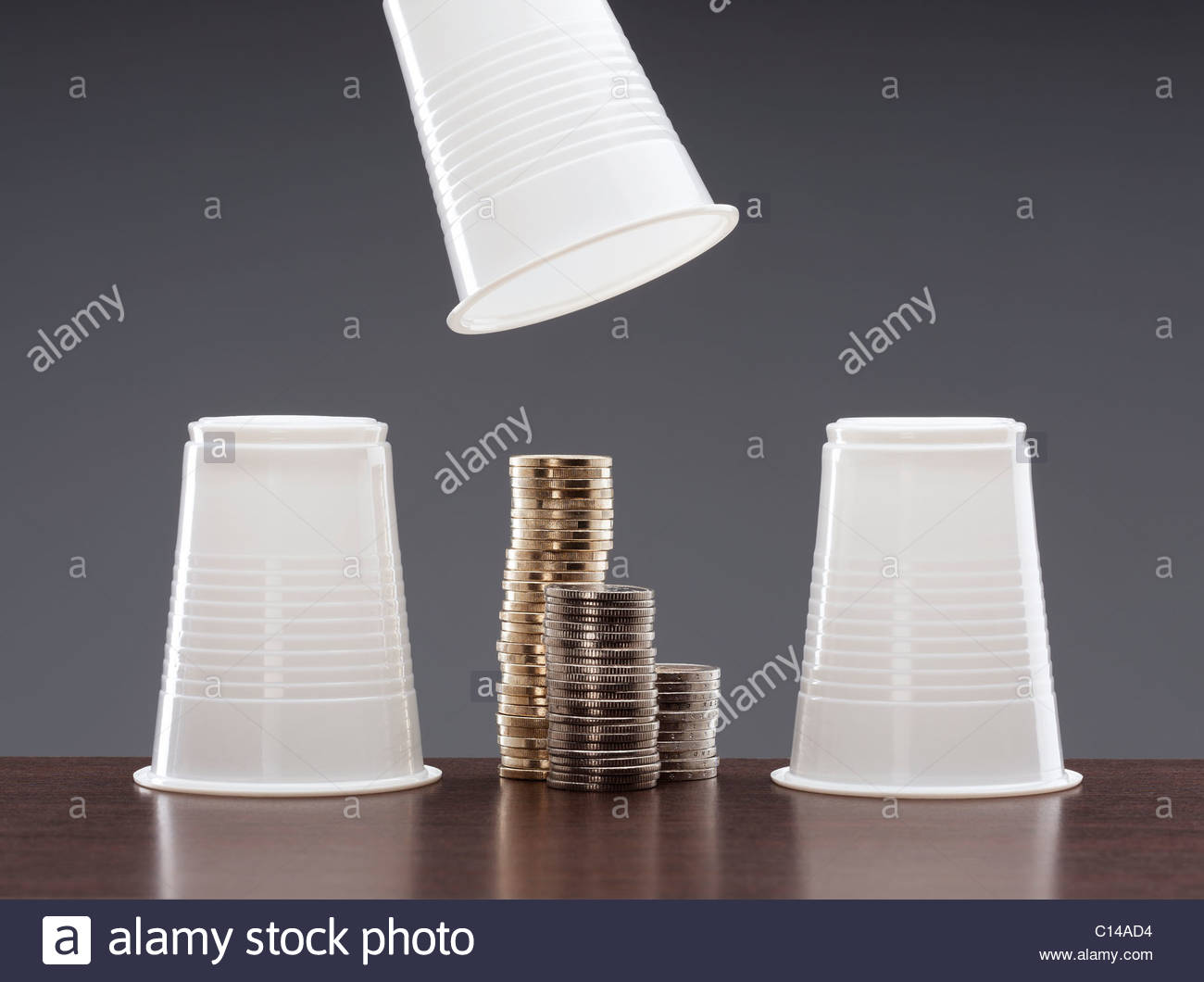 Cups and stacks of coins - Stock Image