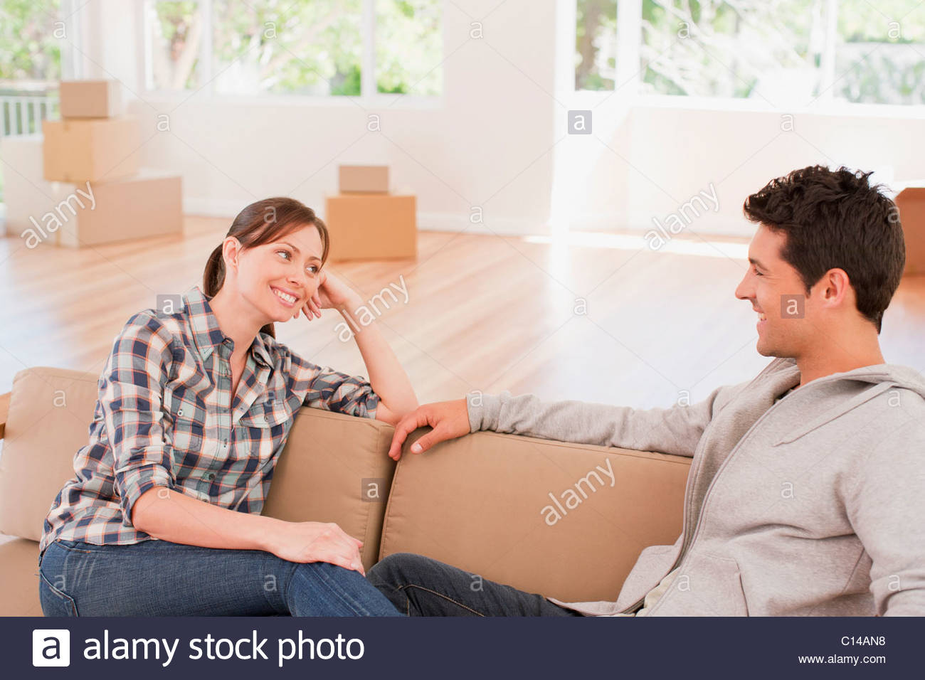 Couple relaxing on sofa in new house - Stock Image