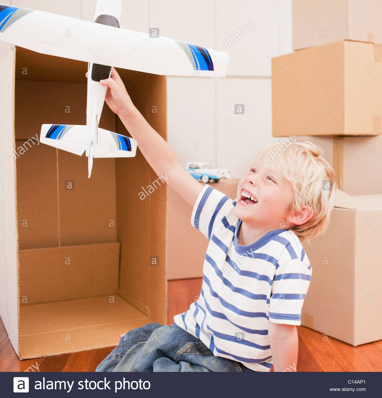 Grinning boy playing with model airplane in his new house - Stock Image