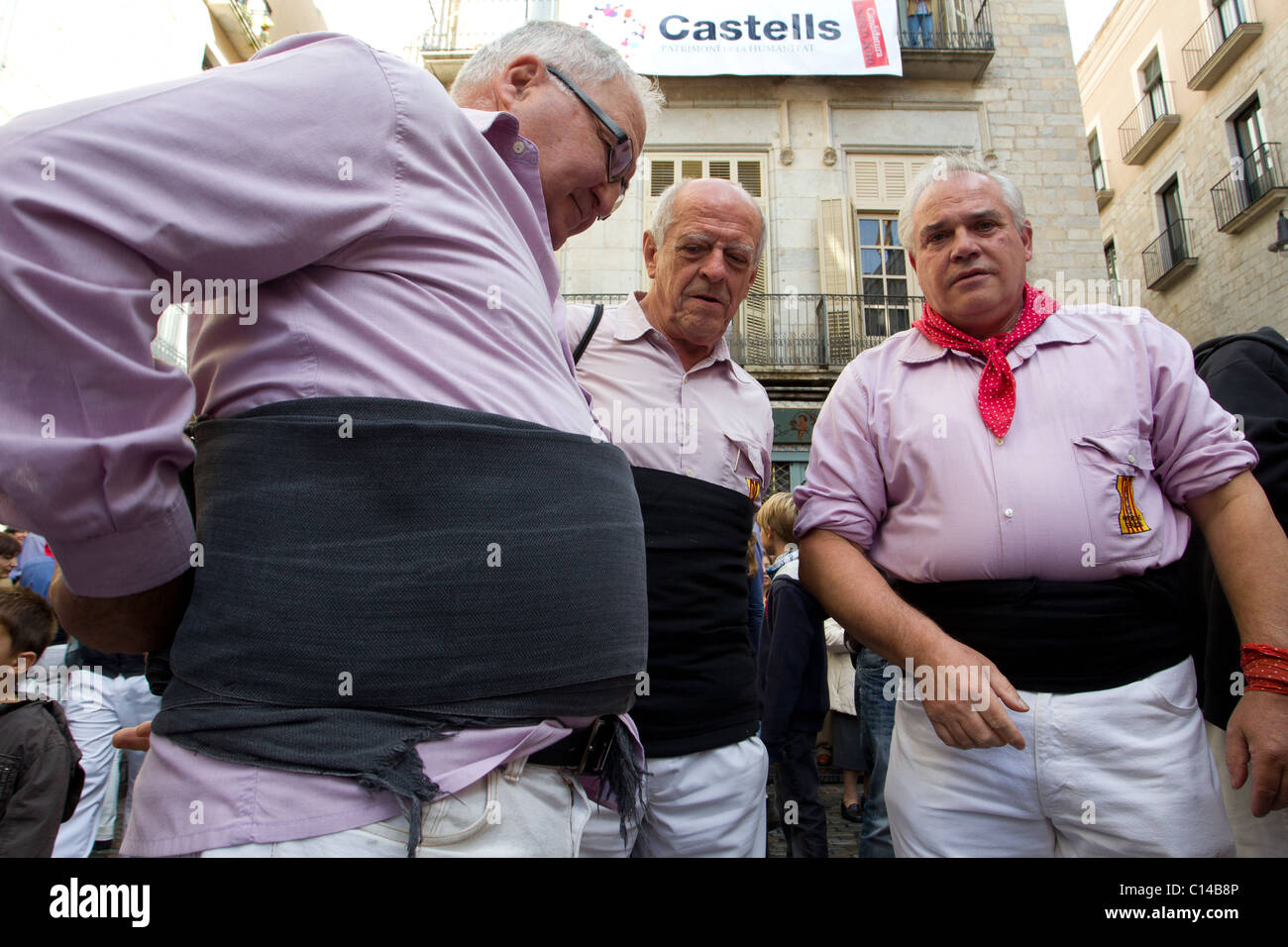 Participants in human tower festival in Catalonia, Spain wrapping waist bands around their stomachs - Stock Image