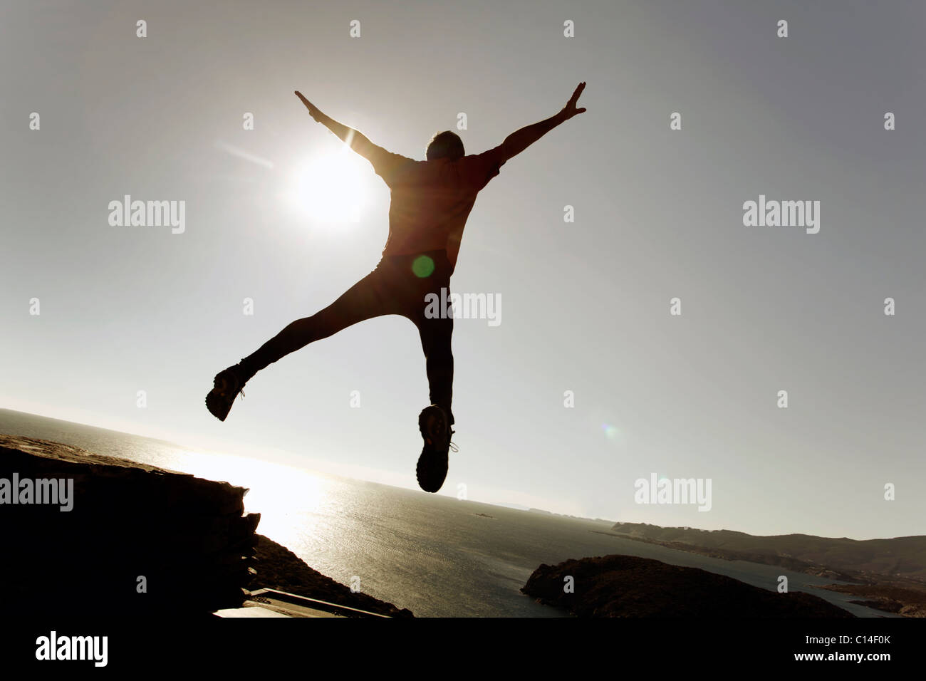 Man leaping through the air by the sea - Stock Image
