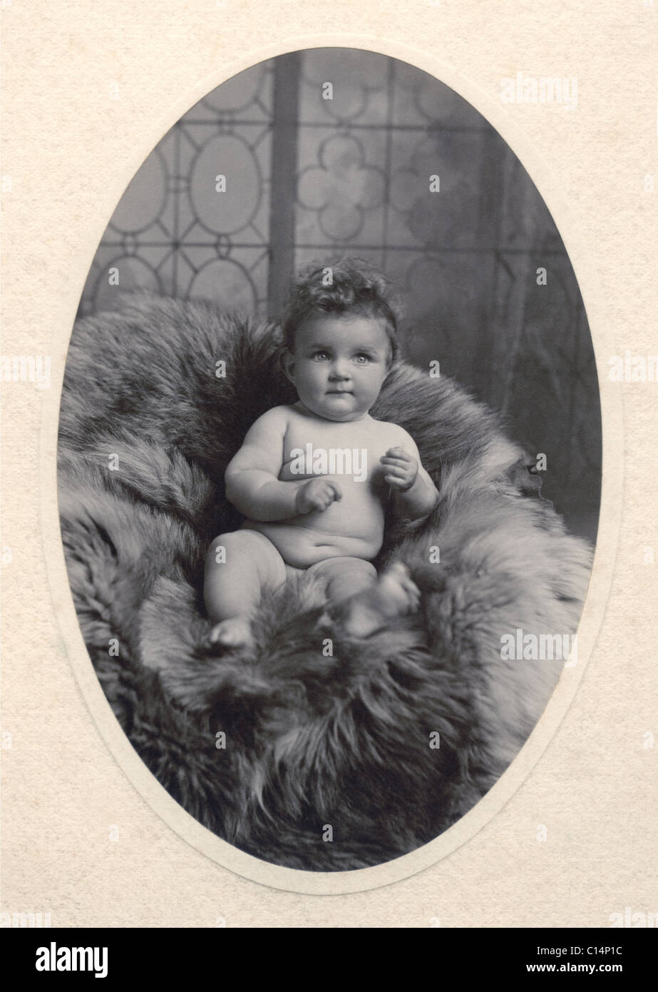 Edwardian or Victorian studio portrait of cute, chubby attractive adorable cherub-like baby with curly hair, lying - Stock Image