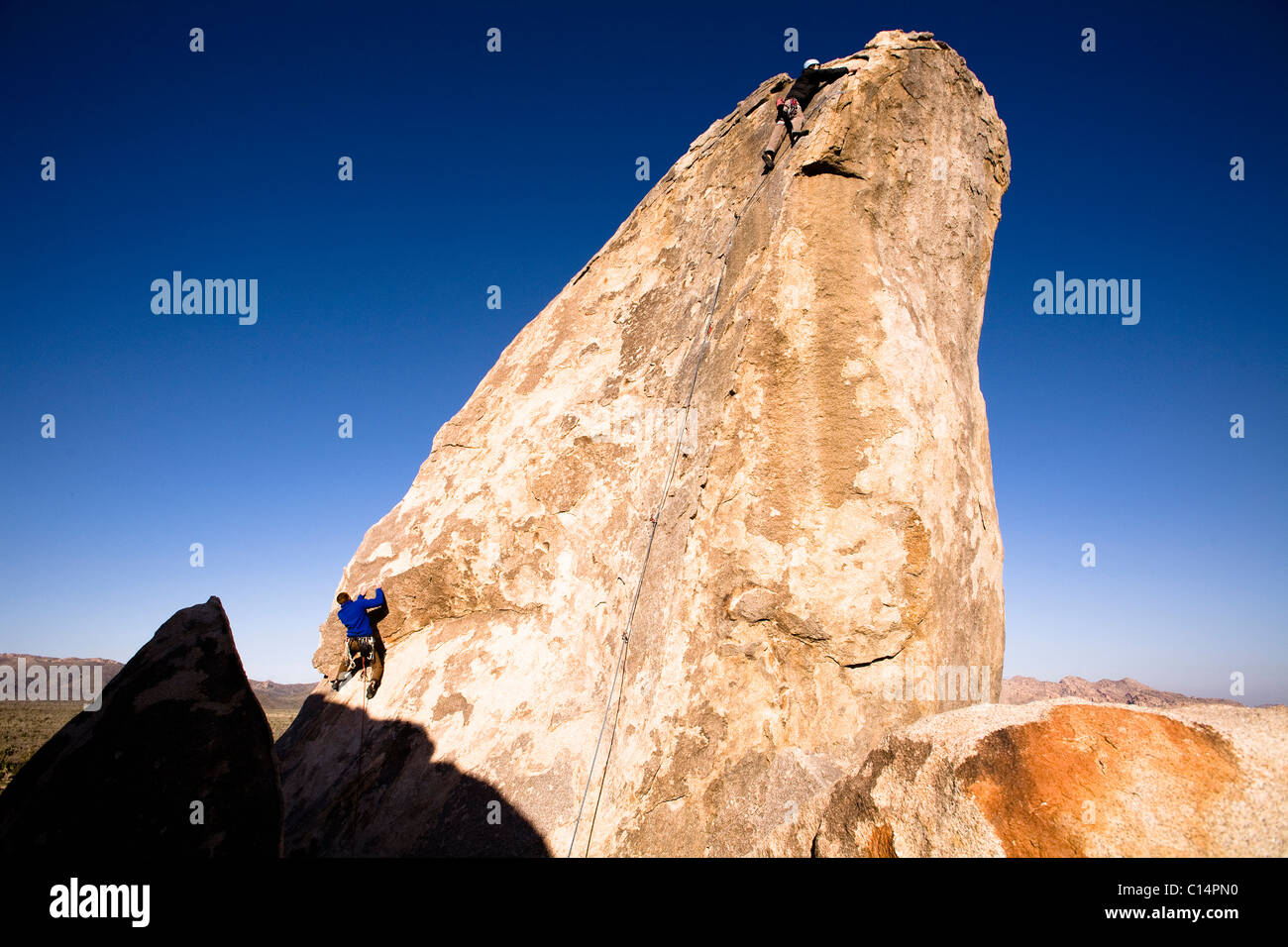 Two male climbers work their way up Headstone Rock in Joshua Tree National Park, California. - Stock Image