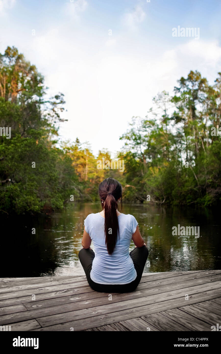 young woman relaxing on a pier looking out over a canal towards the distant trees - Stock Image