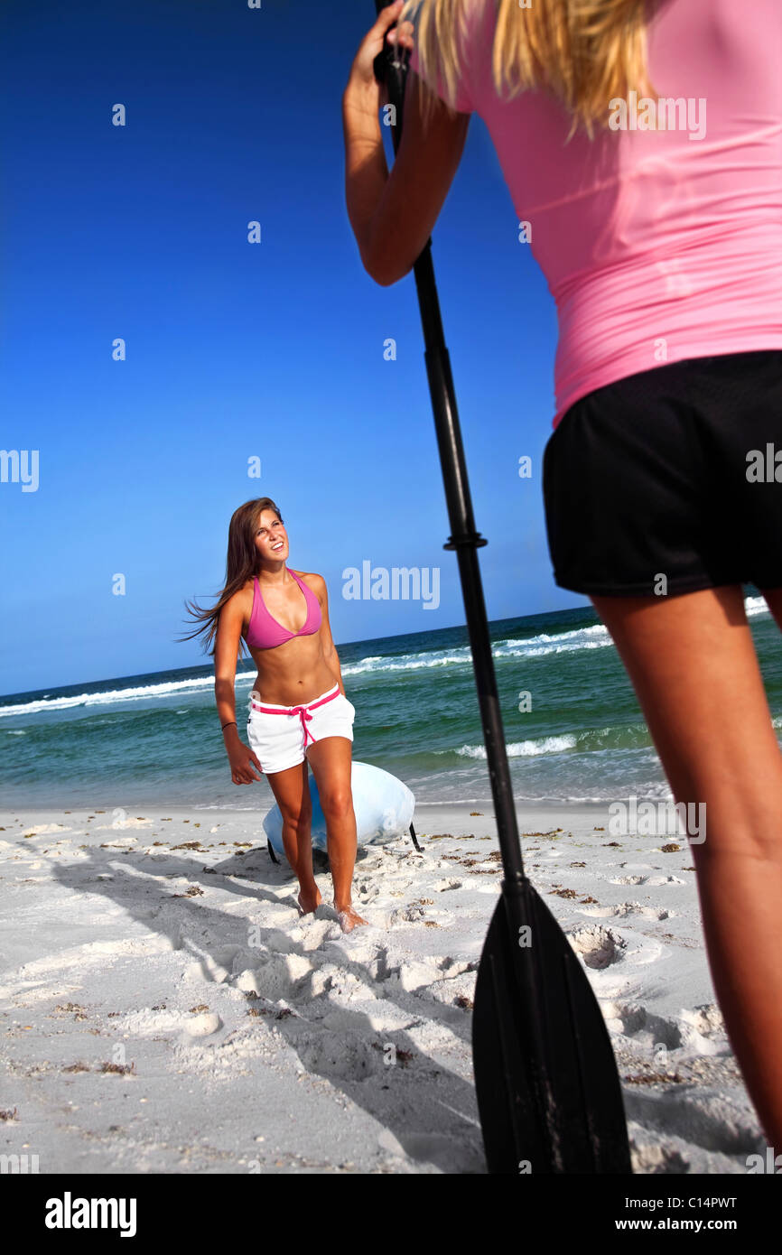 A girl pulls a sea kayak to shore while another teenage girl waits for her in Pensacola Beach, Florida. - Stock Image