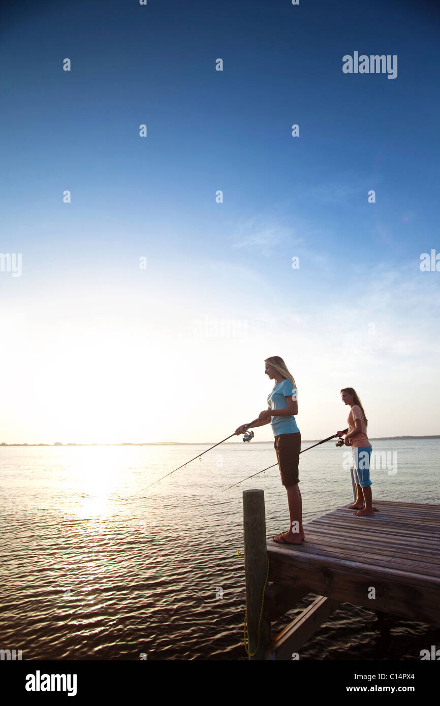 Two girls fish off a pier on the Santa Rosa Sound, Pensacola Beach, Florida at sunset. - Stock Image