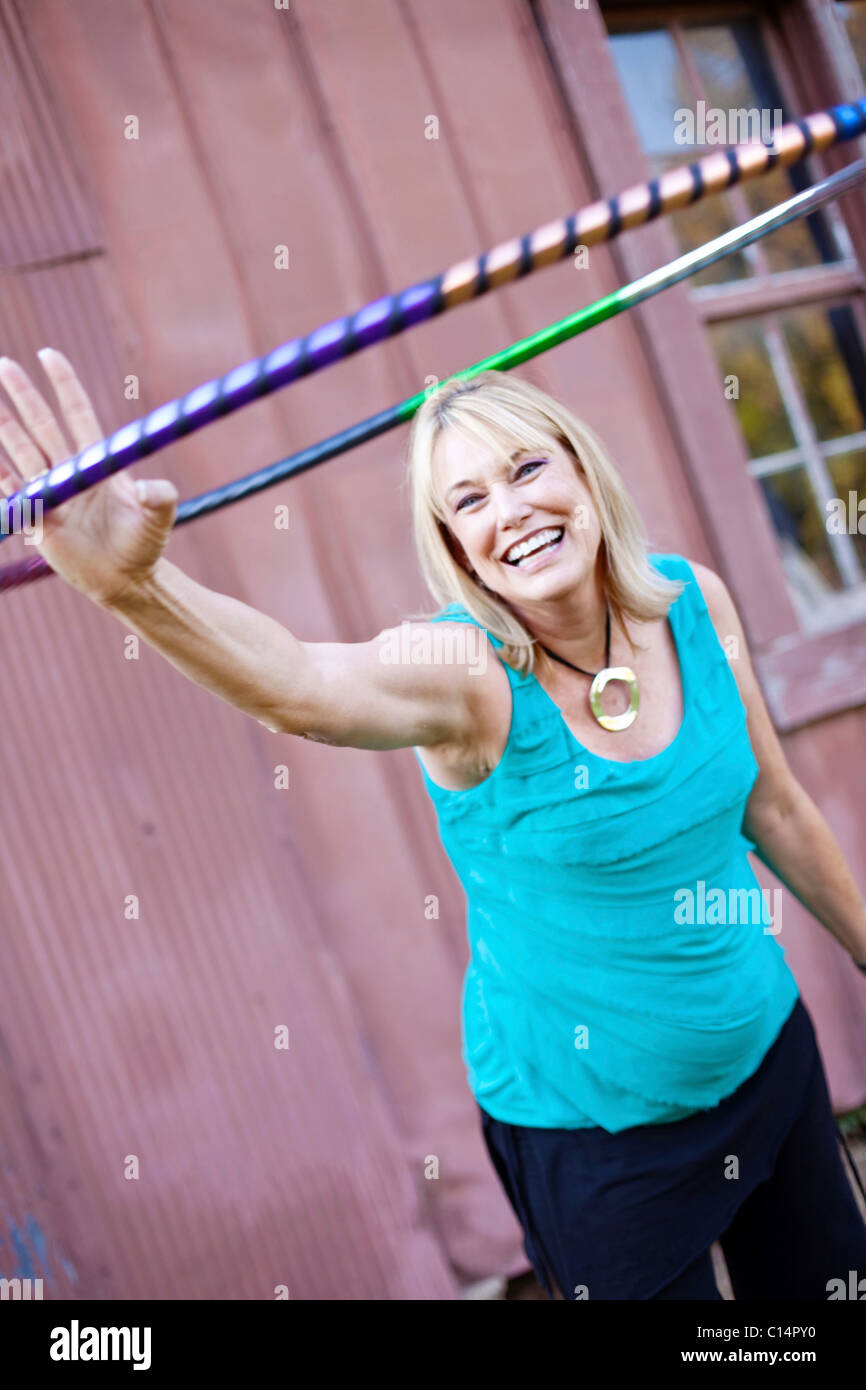 A mature woman extends her arm doing hula hoop exercises in Chelsea, Alabama. - Stock Image