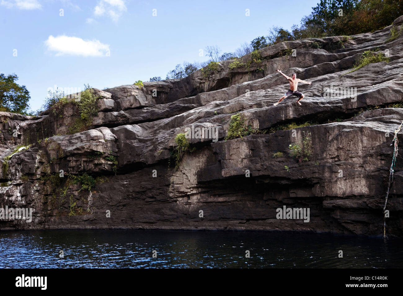 Young man jumps off rock cliffs into a lagoon at High Falls Park, Geraldine, Alabama. - Stock Image