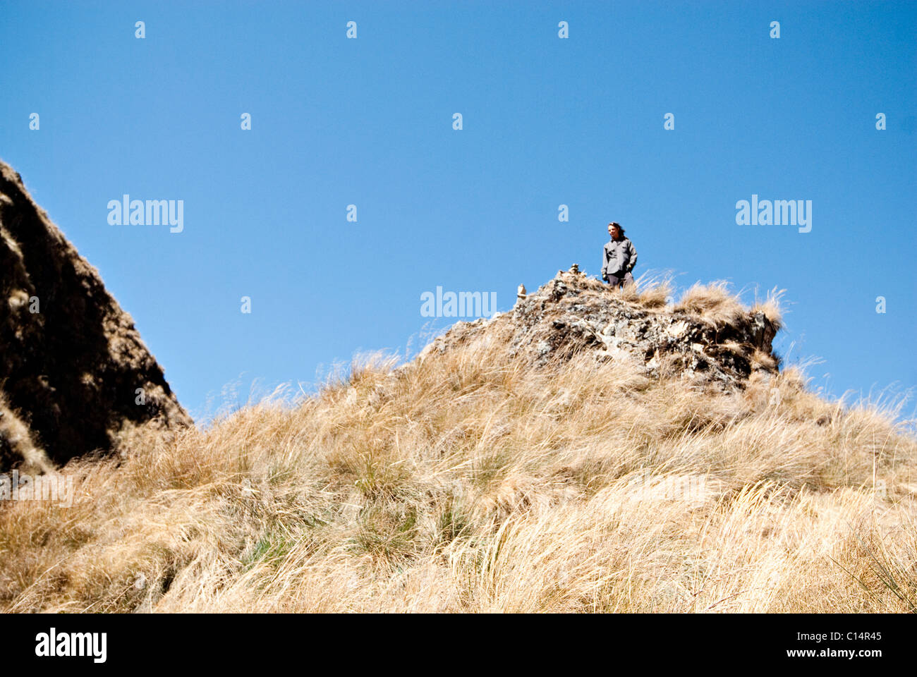 A young man looks into the distance while reflecting on the summit of Dead Woman's Pass, Inca Trail. - Stock Image