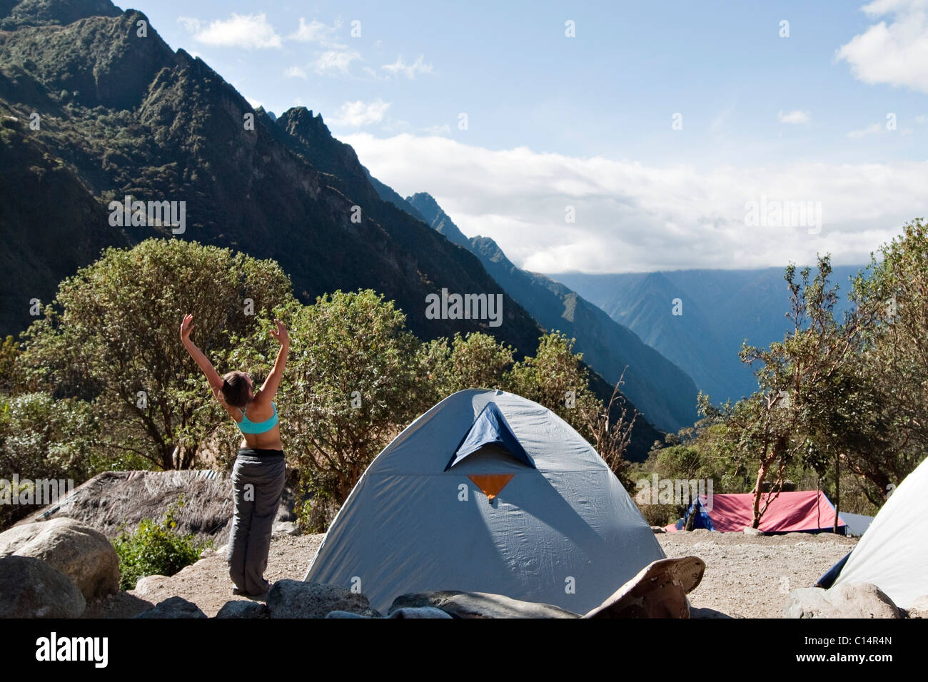 A young woman stretches as she arrives to camp after a long day's hike. - Stock Image