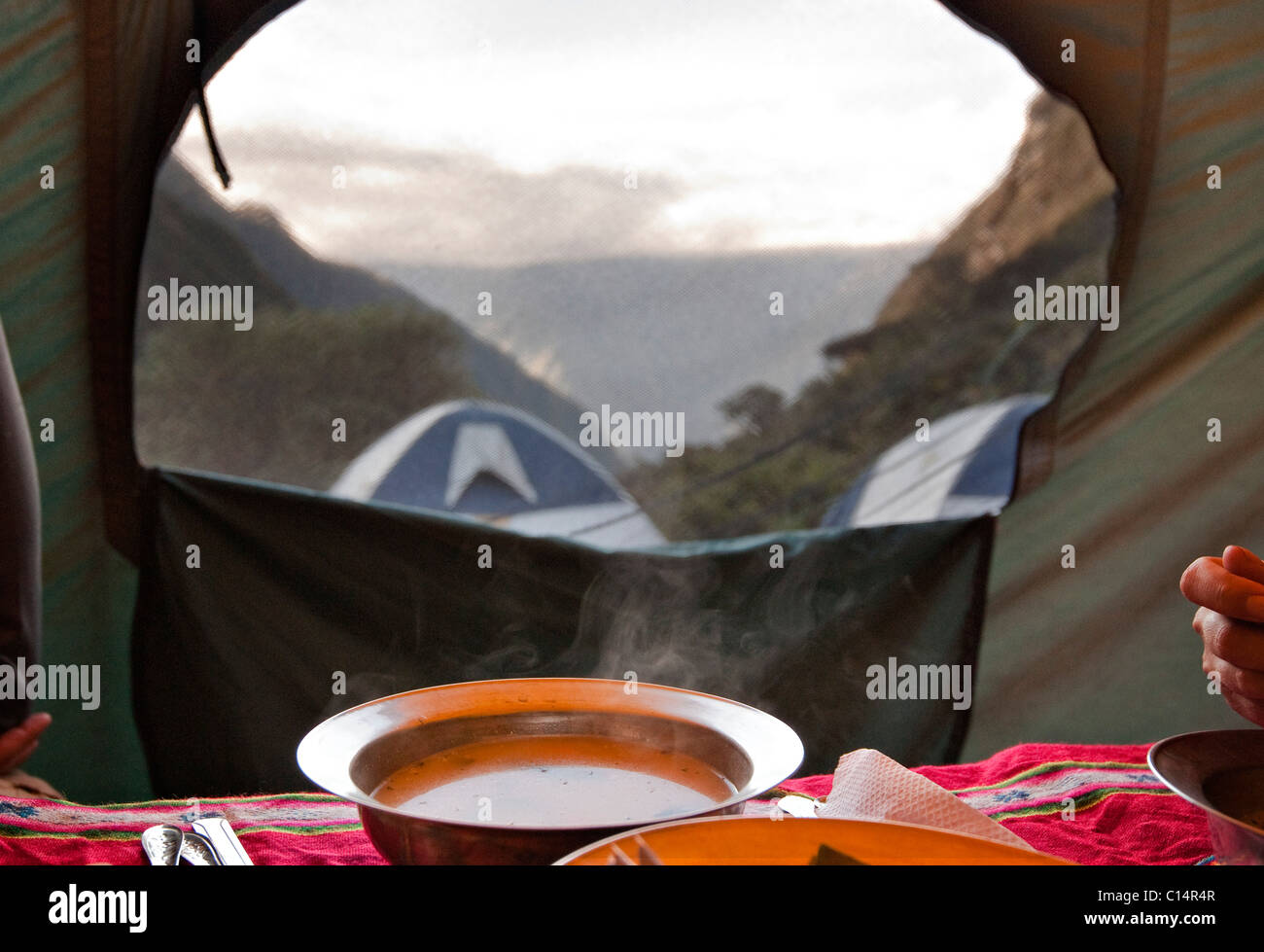 A freshly brewed hot bowl of soup steams in a tent as the sun sets in the Andes Mountains. - Stock Image
