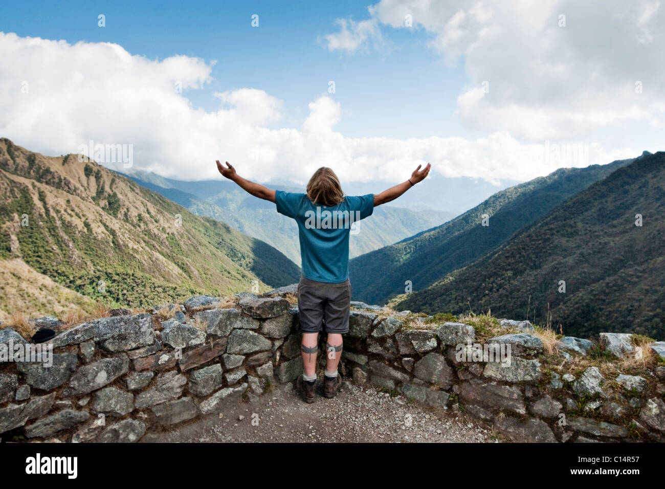 A young man spreads his arms to take in the scenery in the Andes mountains along the Inca Trail. - Stock Image