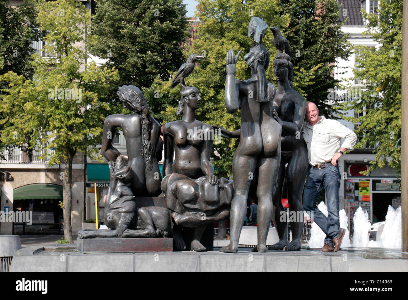 A tourist poses on The Bathing Ladies sculpture, part of main fountain in the Zand Square, Bruges (Brugge), Belgium - Stock Image