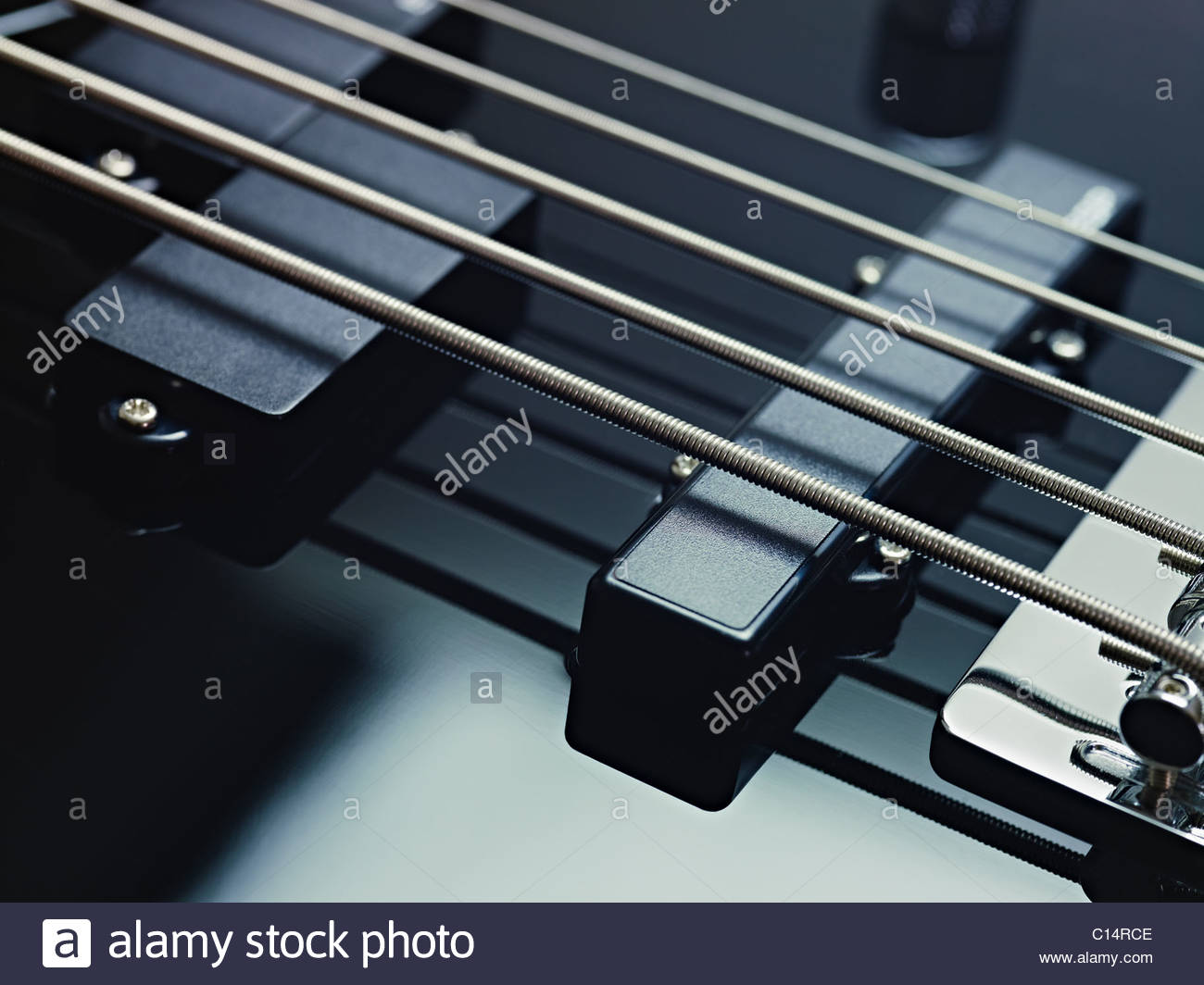 closeup of black five cords electric bass and pickups. Horizontal shape, studio shot - Stock Image