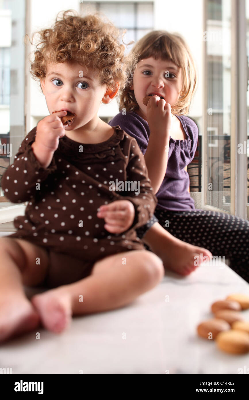 Sisters eat cookies - Stock Image