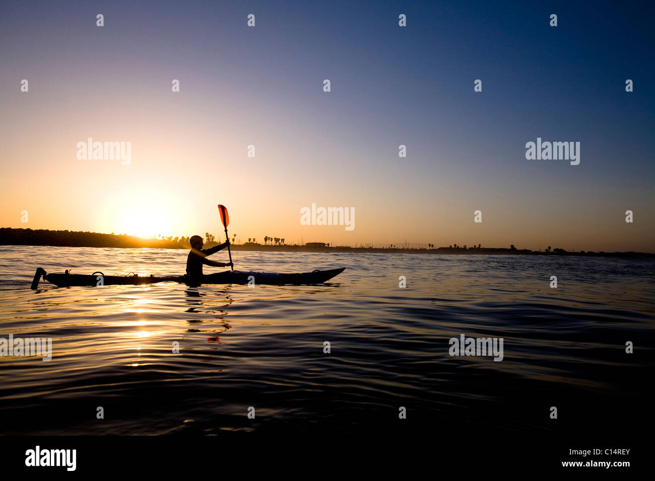 A silhouetted young man paddles a touring kayak just outside of Ventura Harbor in Ventura, California. - Stock Image