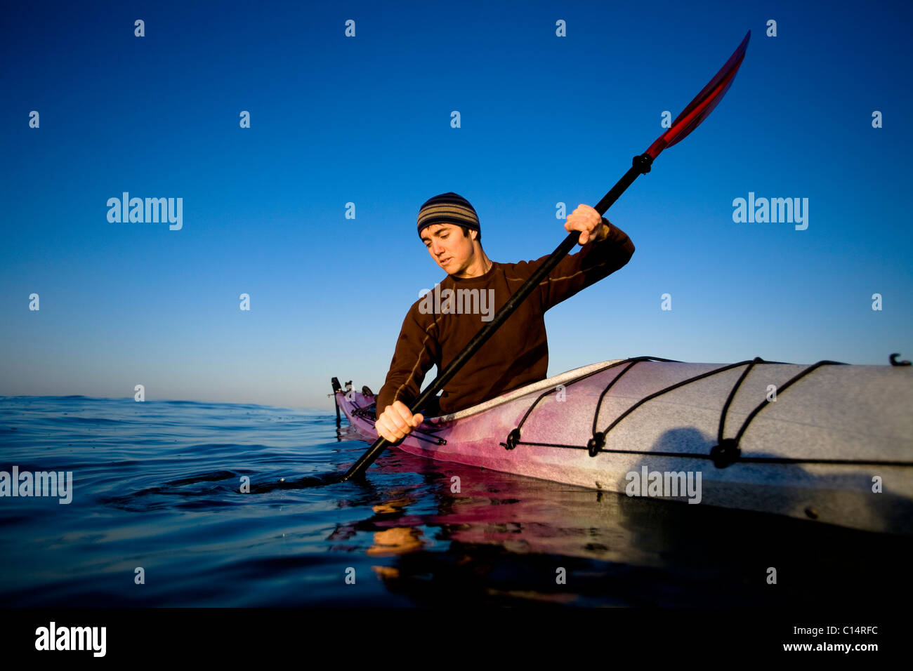 A young man looks at his reflection while paddling a touring kayak just outside of Ventura Harbor in Ventura. - Stock Image