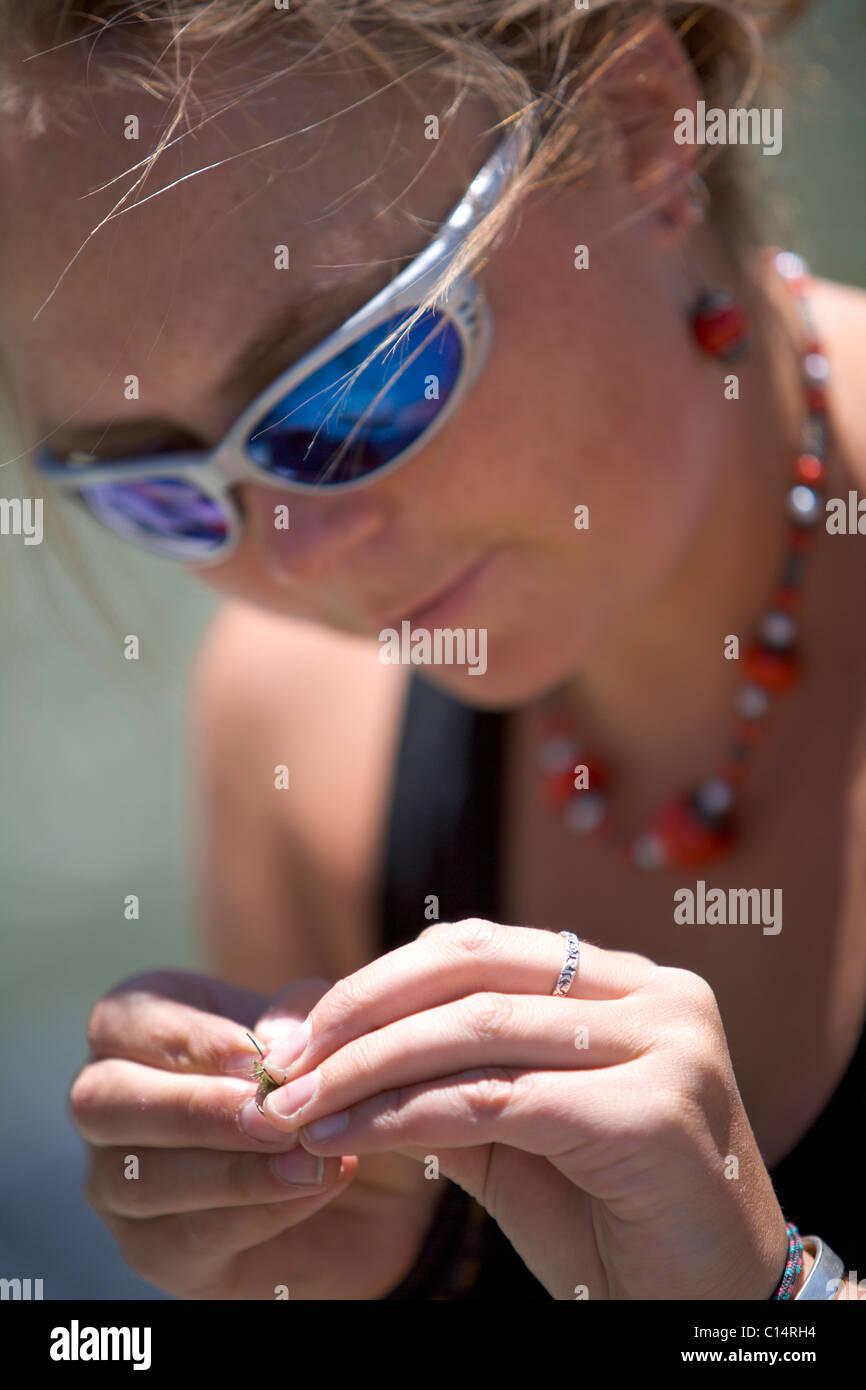 A close up of a female looking down and tying a fly to her line. Stock Photo