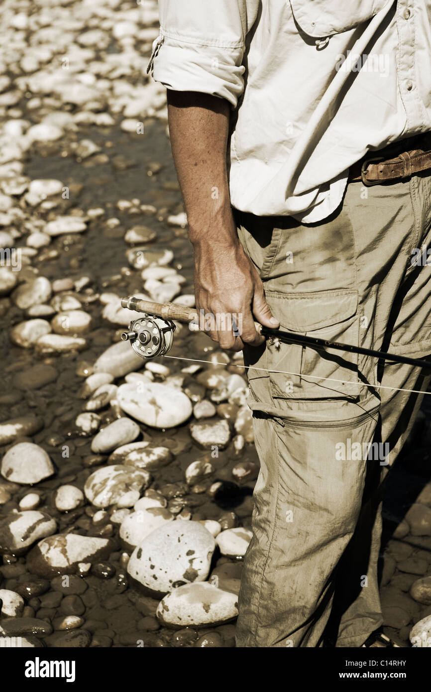 A fisherman holds his fly fishing rod on his side with white river rocks behind him. Stock Photo