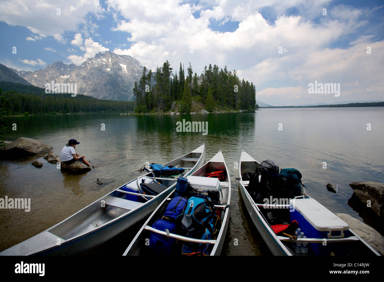A boy sits contemplating on a lake rock while looking at the Grand Tetons. - Stock Image