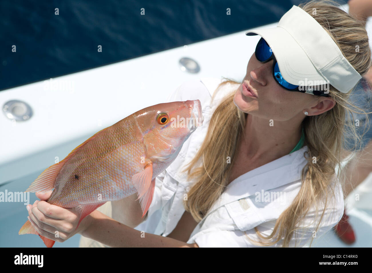 A blonde woman with a white hat and sunglasses holds a freshly caught red snapper and blows it a kiss. - Stock Photo
