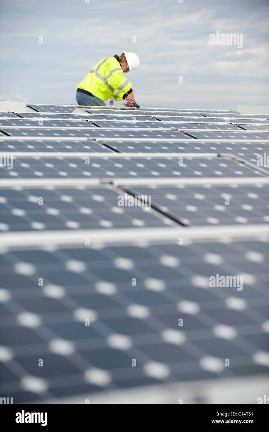Green energy technician adjusts photovoltaic panels on a roof - Stock Image