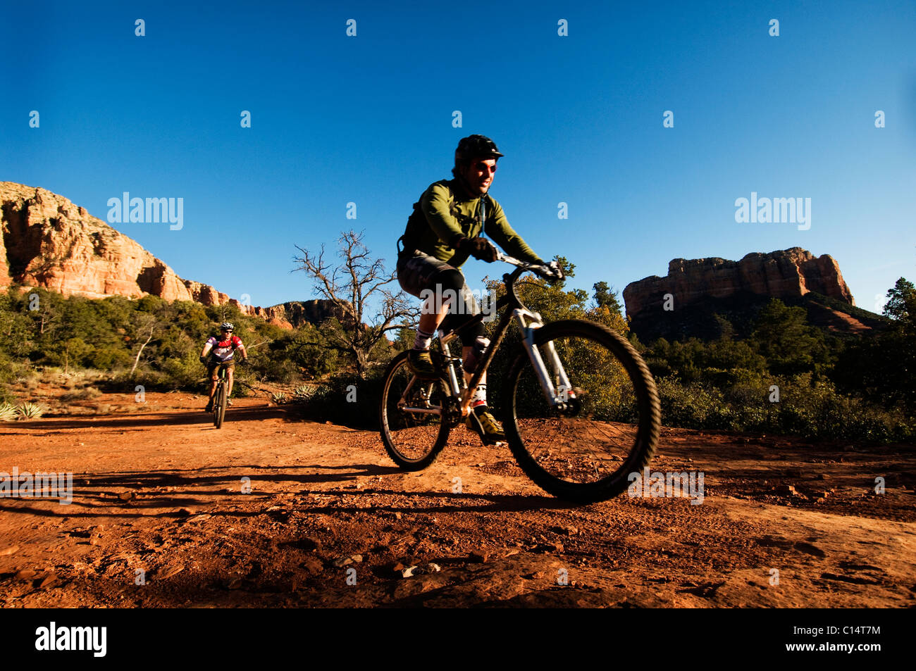 Two middle age men ride mountain bikes through the red rock country of Sedona, AZ. - Stock Image