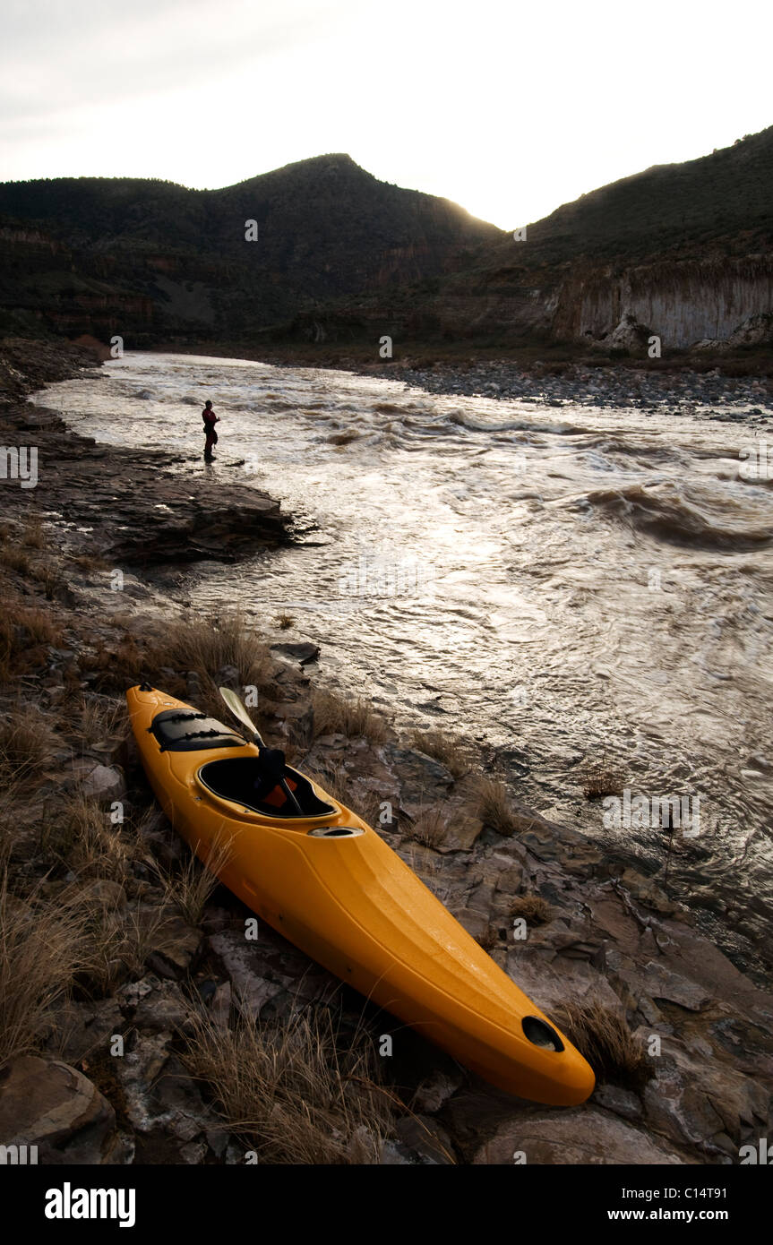 A whitewater kayak rests on the shore after a surf session in Ledge Rapid on the Salt River, AZ. - Stock Image