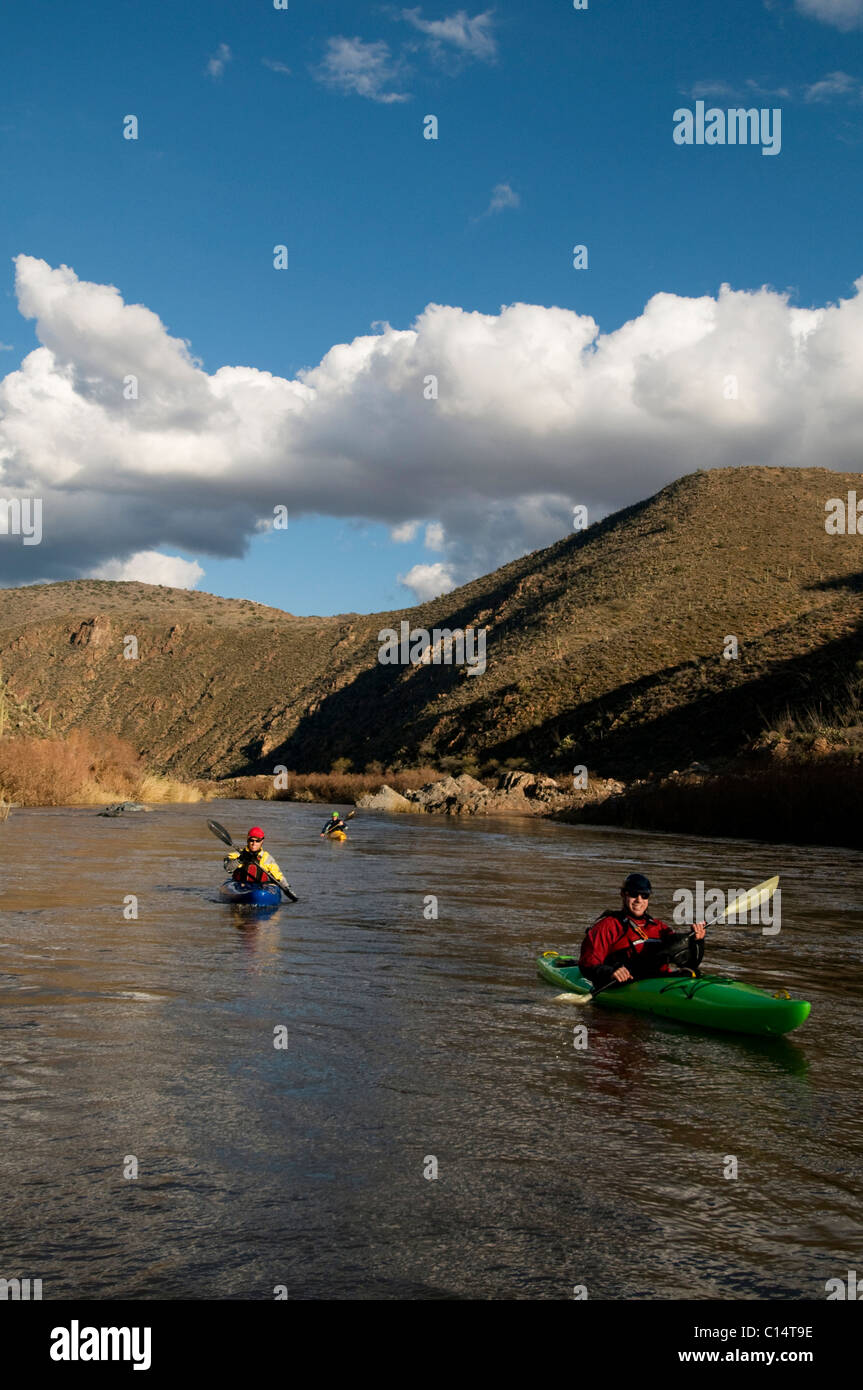 Whitewater kayakers paddle downstream during a whitewater rafting trip on the Salt River, AZ. - Stock Image