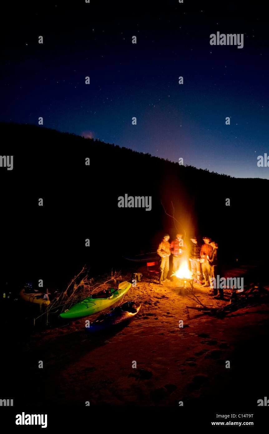 River runners huddle around the fire and swap stories during a winter river trip down the Salt River, AZ - Stock Image