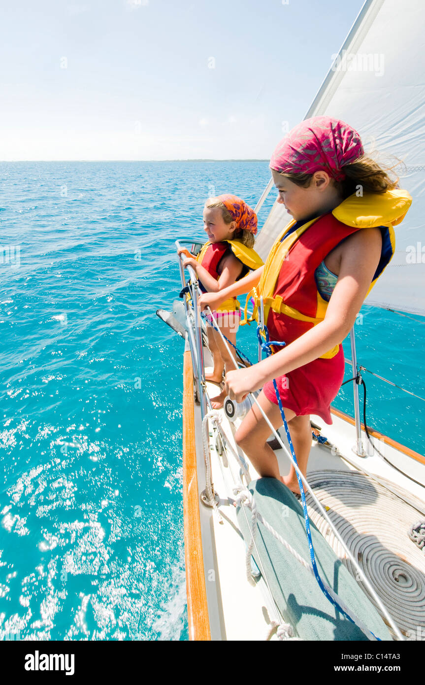 Two young girls on the bow during a day sail in Georgetown, Exumas - Stock Image