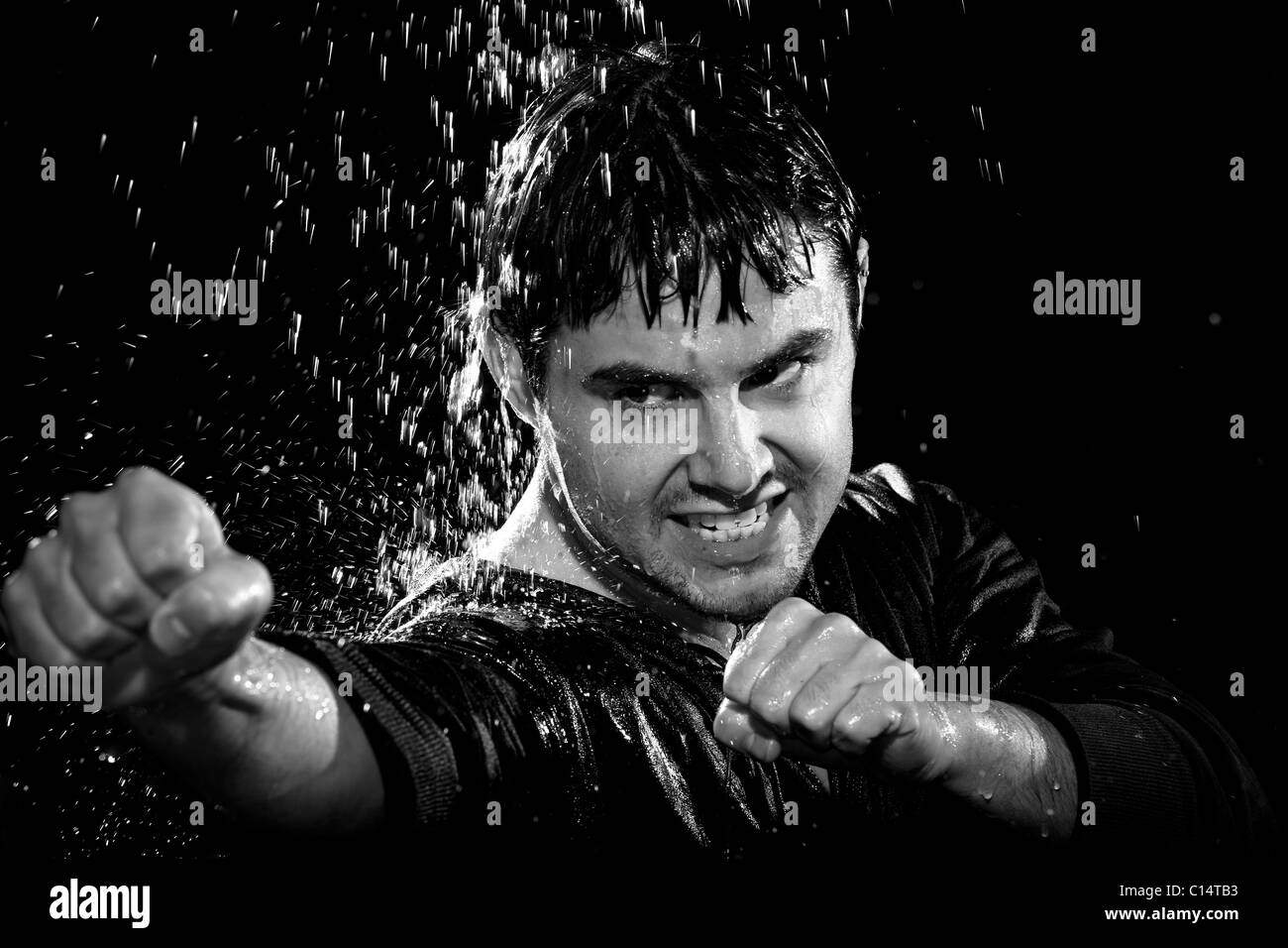 A young man wearing a jacket poses in a wushu stance while it rains down on him. - Stock Image