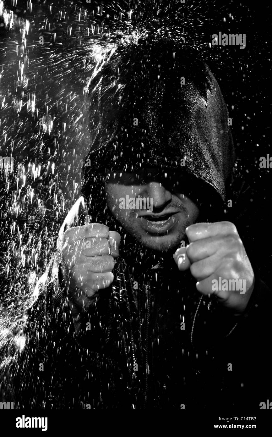 A young man wearing a hooded jacket poses in a wushu stance while it rains down on him. - Stock Image