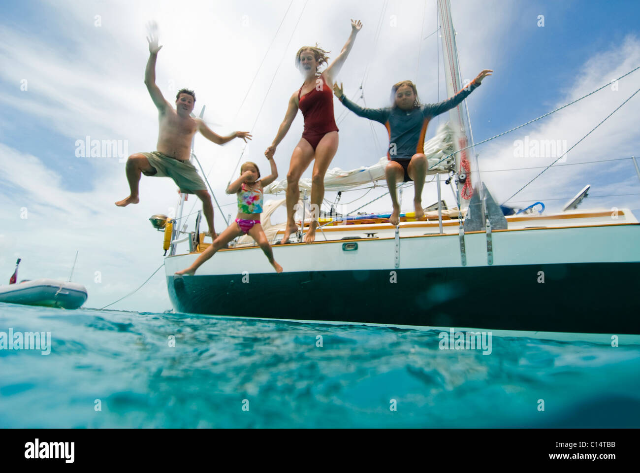 A family jumping off their boat - Stock Image