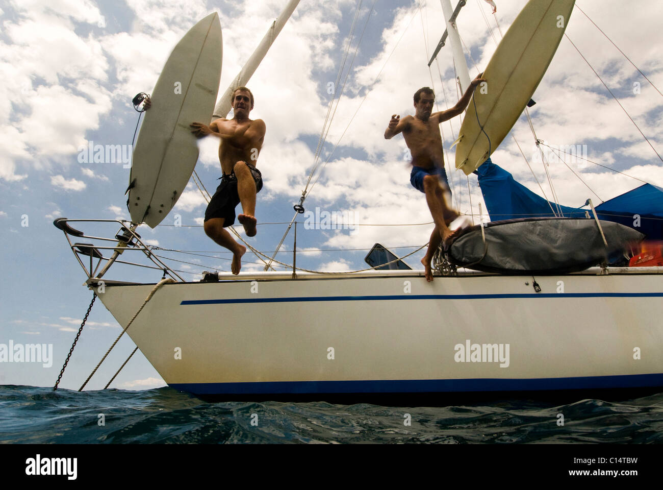 Two guys jumping off their boat heading out for surf in Costa Rica - Stock Image