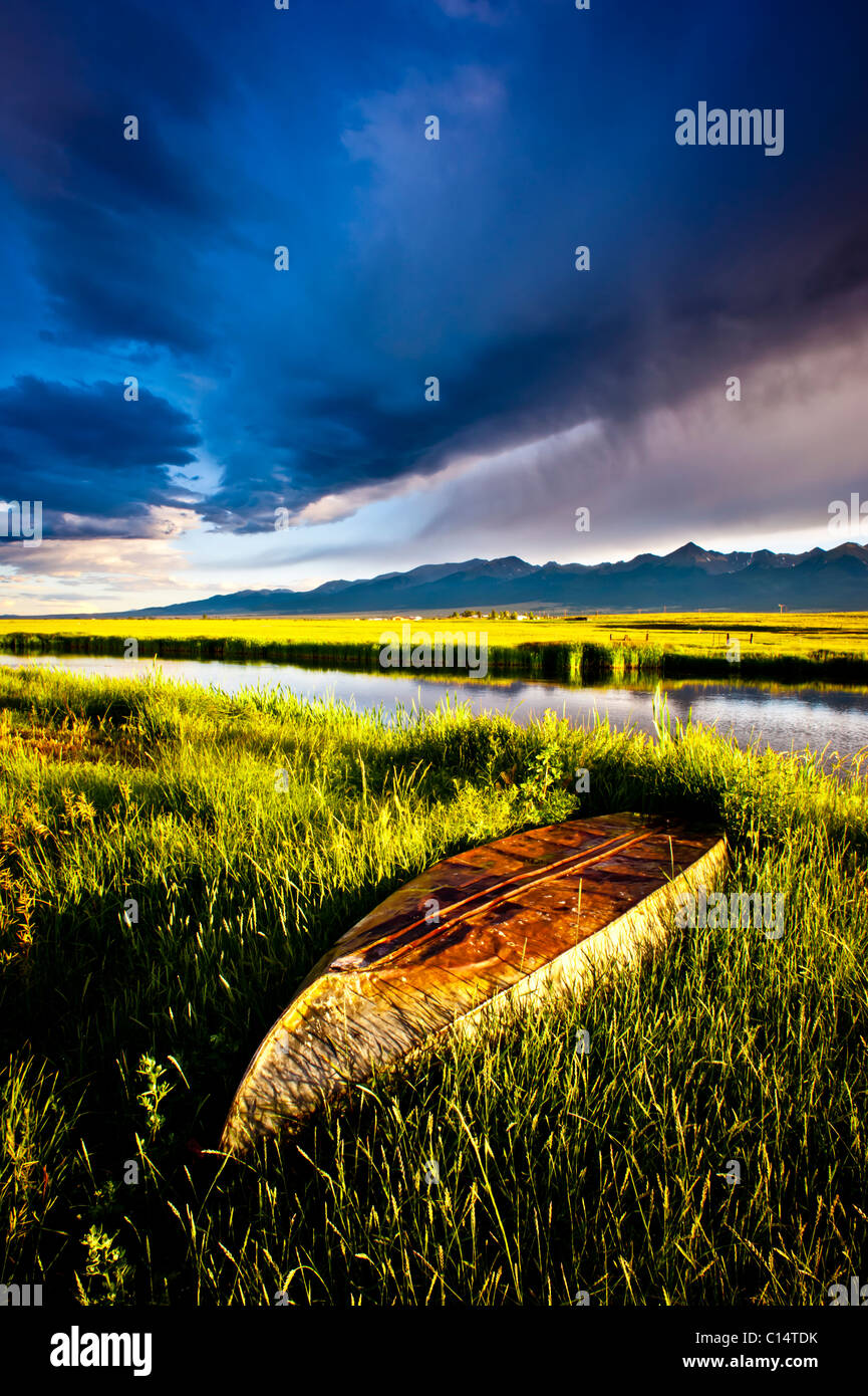 Boat in green grass with pond, mountains and stormy sky.  Westcliffe, Colorado. - Stock Image