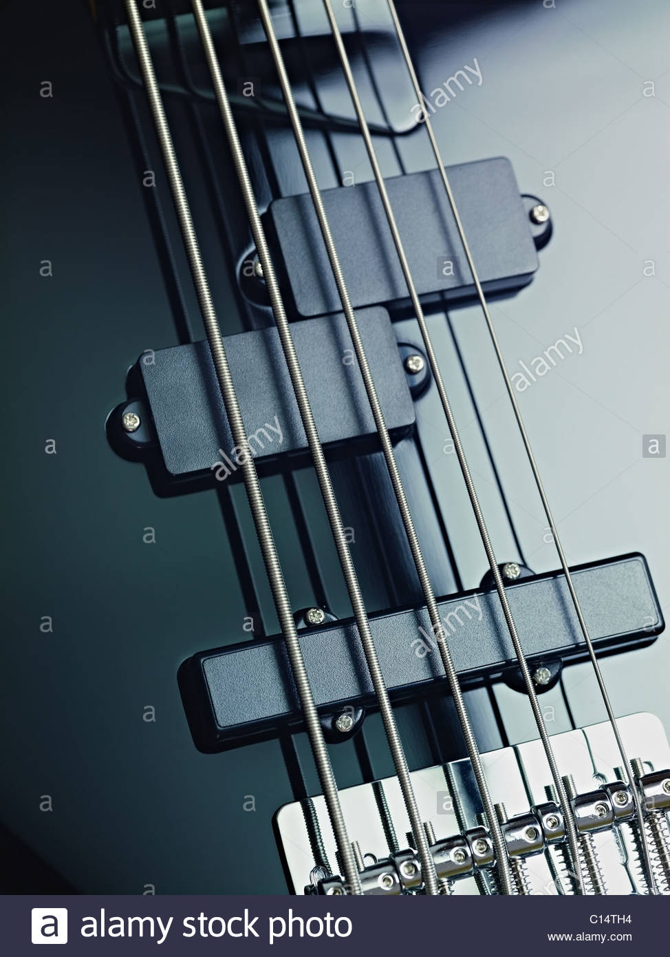 closeup of black five cords electric bass and pickups. Vertical shape, studio shot - Stock Image