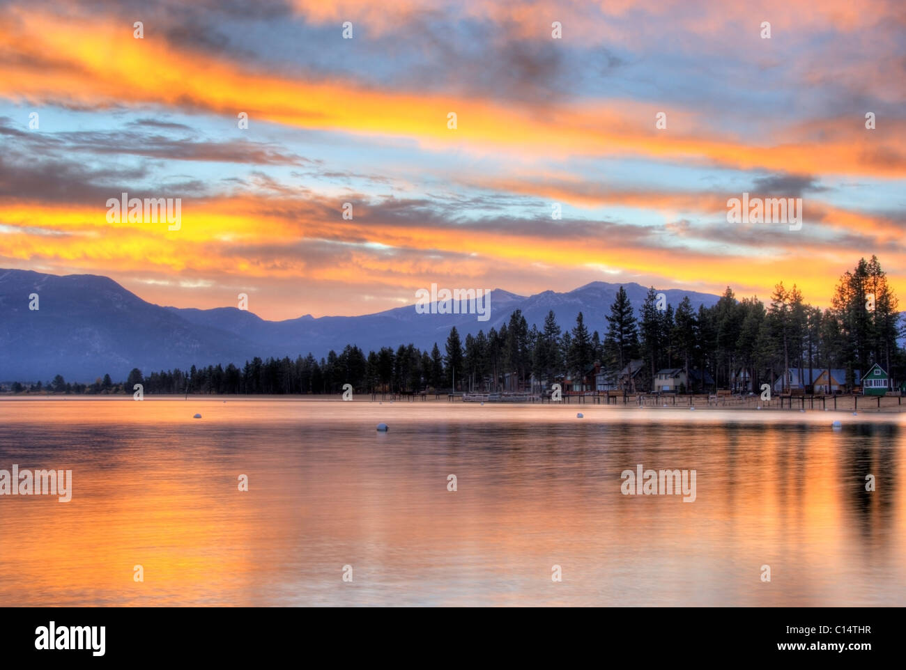 A brilliant fall sunrise is reflected in Lake Tahoe, California. - Stock Image