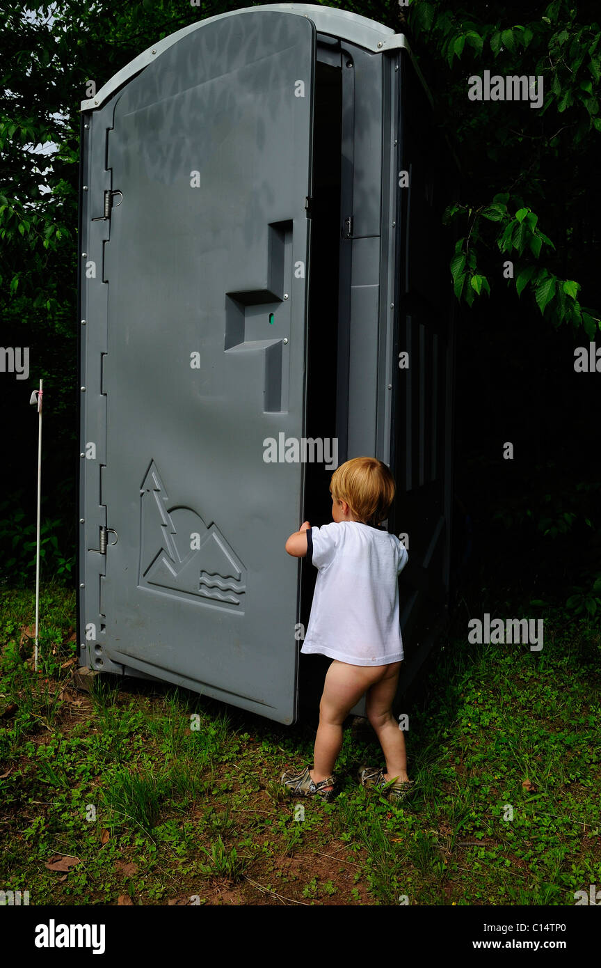 young boy opens door on portable toilet Stock Photo