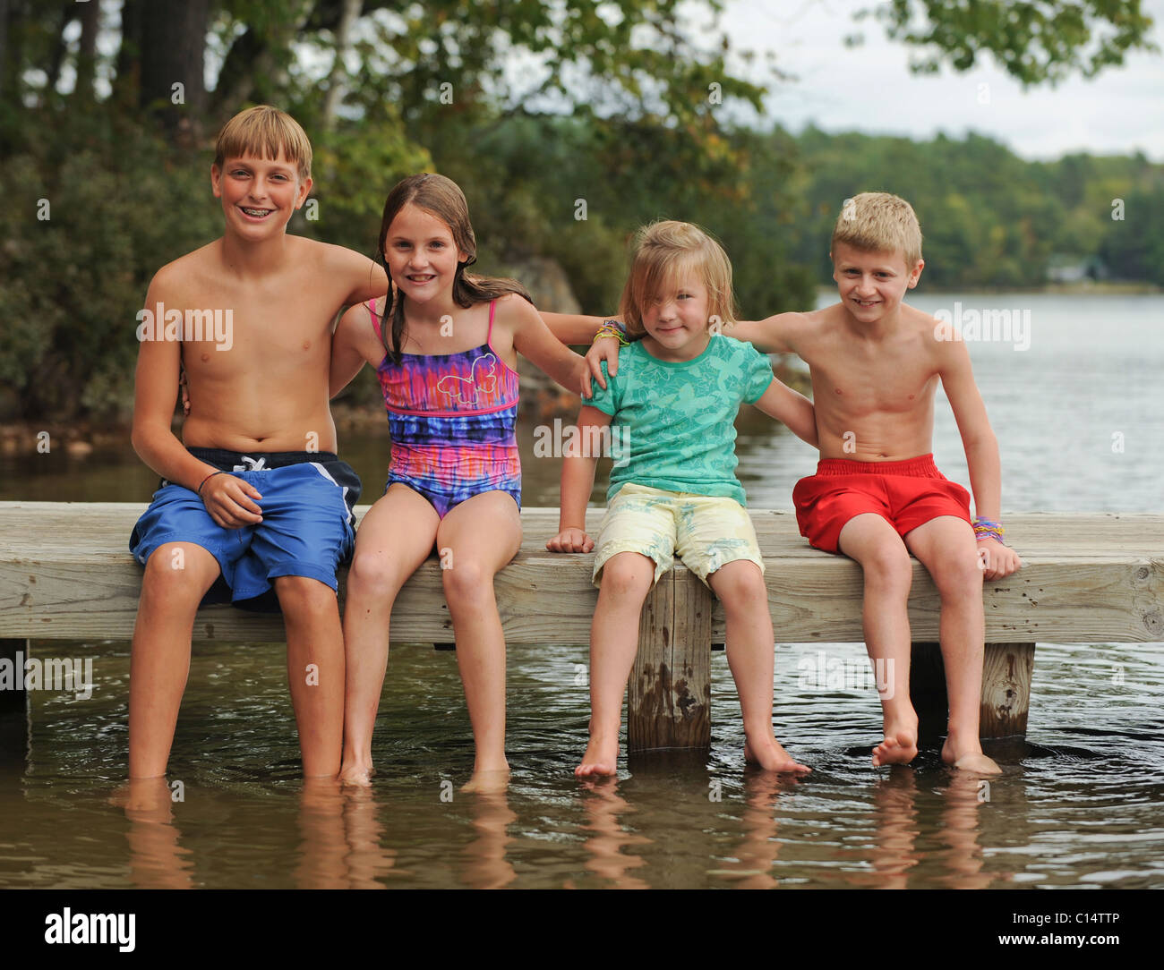 Maine Camp Life: Four children dangle their feet in the water off a pier at Crystal Lake near Harrison, Maine. - Stock Image