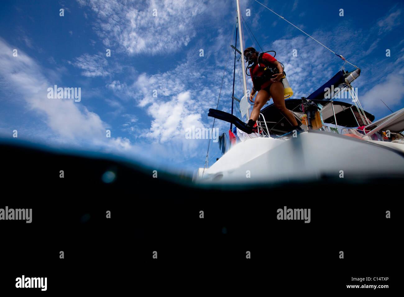 A young Hispanic woman in scuba gear jumps off a catamaran. - Stock Image