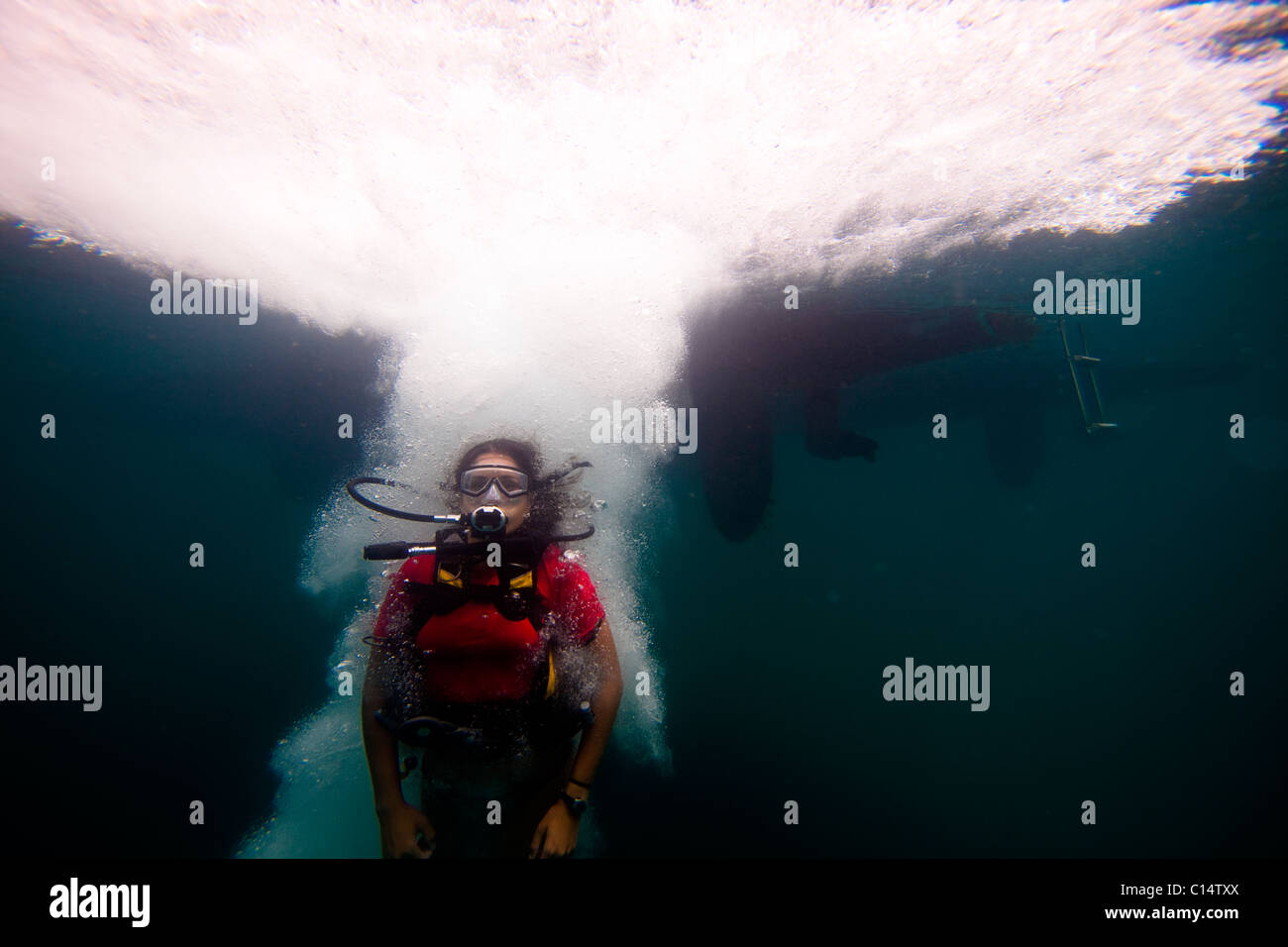 A young Hispanic woman in scuba gear jumps into the ocean. - Stock Image